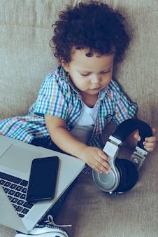Ho davvero bisogno di tutti questi gadget! vista ad alto angolo del piccolo bambino africano che tiene le cuffie mentre è seduto sul divano di casa con laptop e smartphone sulle ginocchia