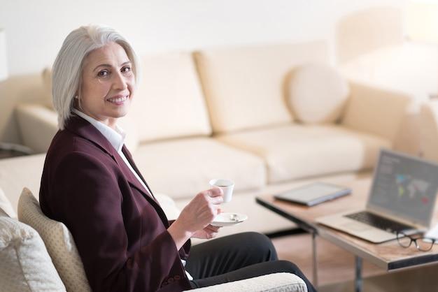 Mi rilasso. felice imprenditrice invecchiata felice sorridendo e bevendo un caffè mentre era seduto in ufficio davanti al computer portatile ed esprimendo gioia