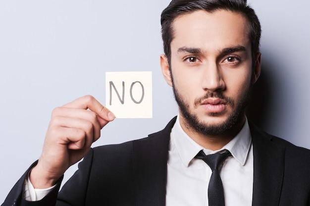 Ho detto di no. bel giovane in abiti da cerimonia che tiene una nota adesiva mentre sta in piedi su uno sfondo grigio