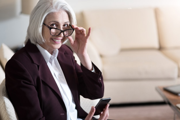 Ti vedo. affascinante donna di affari invecchiata felice che tiene il telefono e gli occhiali mentre era seduto in ufficio ed esprimeva felicità