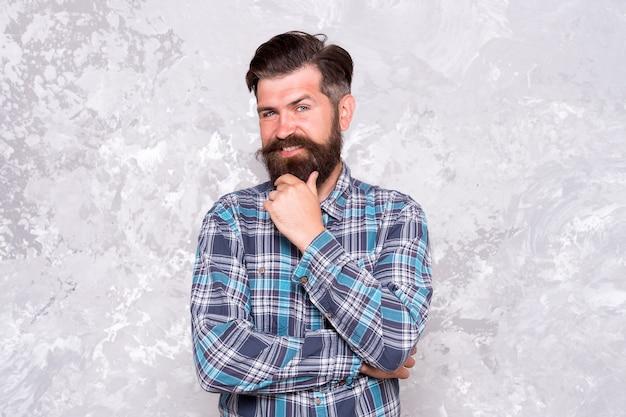 Credo di si. fiducioso hipster in camicia a scacchi. stile hipster. vestito hipster ragazzo. maturo e trendy. tratti maschili. fondo concreto dell'uomo barbuto brutale. uomo serio con barba e baffi.
