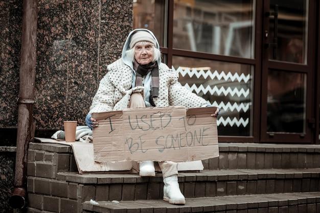 Ero qualcuno. donna senzatetto infelice che ti guarda mentre tiene un cartello tra le mani