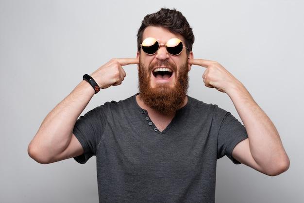 Non voglio sentire niente. giovane uomo barbuto che copre le sue orecchie di dito indice che indossa i vetri di sole su fondo bianco.