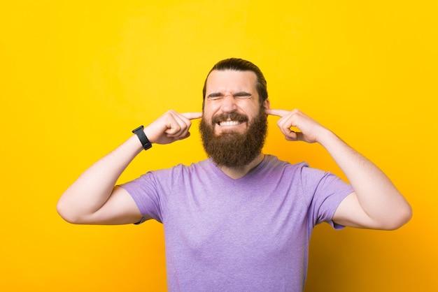 Non voglio sentirti. il giovane uomo barbuto ha messo le dita nelle orecchie.