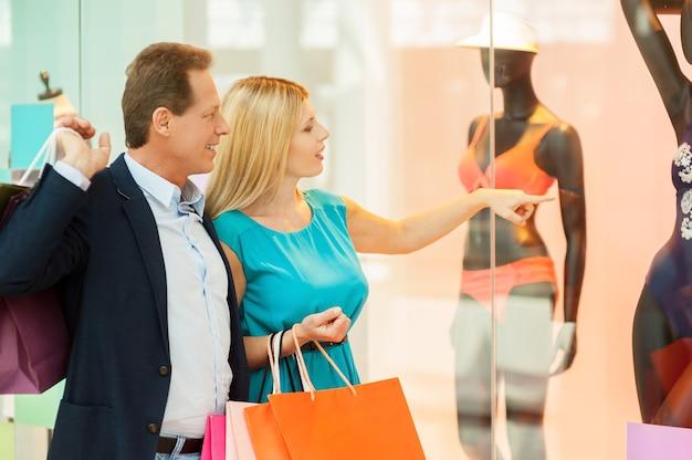 Voglio questo! coppia matura allegra che fa shopping nel centro commerciale mentre la donna indica il manichino