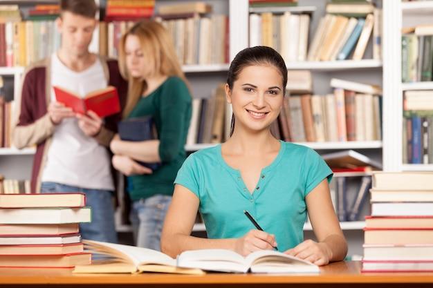 Sarò pronto per il mio esame finale. fiduciosa giovane donna seduta alla scrivania della biblioteca e sorridente mentre due persone leggono un libro sullo sfondo