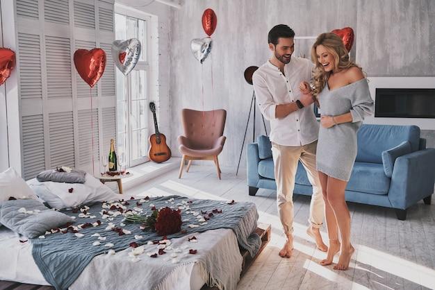 Sarò il tuo valentino. per tutta la lunghezza della giovane donna sorpresa che sorride mentre sta in piedi con il suo ragazzo nella camera da letto piena di palloncini