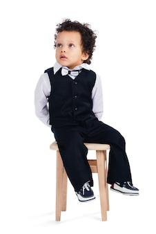 Mi siedo qui e non faccio niente! piccolo neonato africano che guarda lontano mentre è seduto su uno sgabello su sfondo bianco