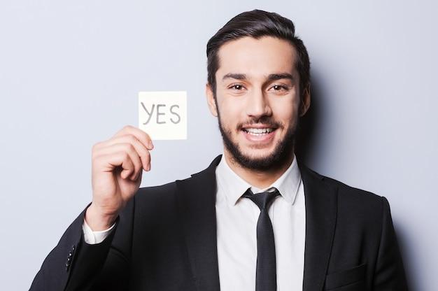 Dirò di sì! bel giovane in abiti da cerimonia che tiene una nota adesiva mentre sta in piedi su uno sfondo grigio