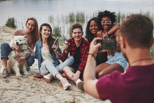 Ti farò una foto in un secondo. un gruppo di persone fa un picnic sulla spiaggia. gli amici si divertono durante il fine settimana.
