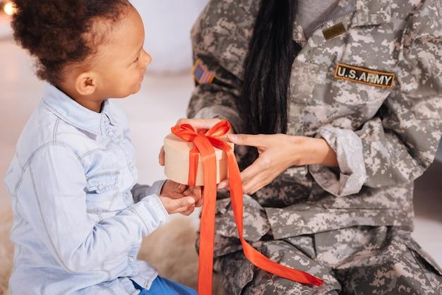 L'ho avvolto io stesso. incredibile dolce bambina energica che dà a sua madre una scatola segreta salutandola al suo arrivo mentre trascorre alcune settimane a casa