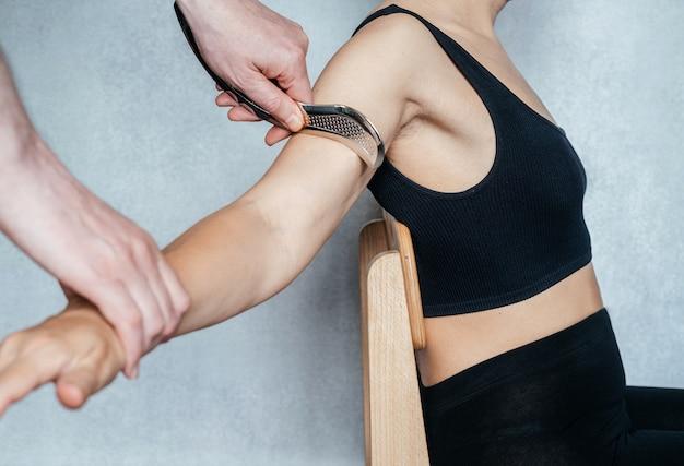 Trattamento iastm per restrizione miofasciale, una donna che riceve un trattamento dei tessuti molli sul braccio con strumento guasha iastm in acciaio inossidabile