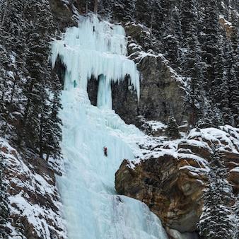 Scalatore di ghiaccio sulla cascata congelata, lake louise, parco nazionale di banff, alberta, canada