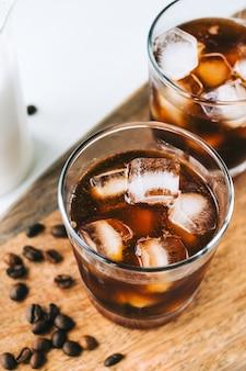Ice coffee americano in vetro con cubetti di ghiaccio su tavola di legno, primo piano