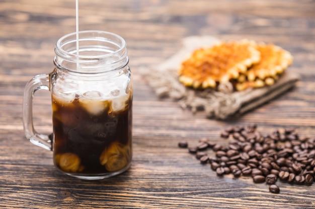 Caffè ghiacciato e chicchi di caffè sullo sfondo.