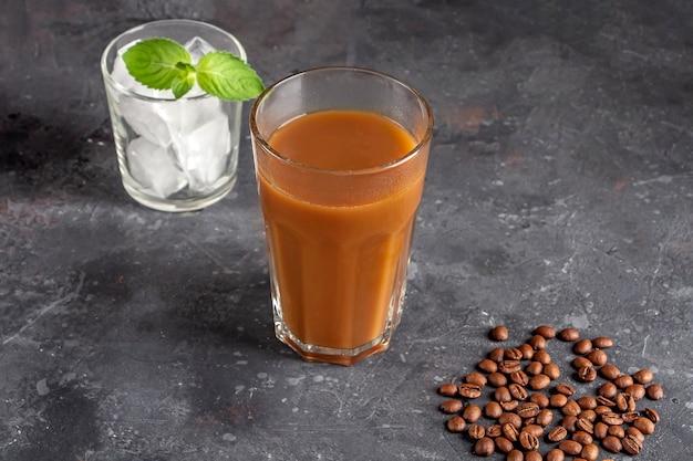 Caffè freddo con menta e latte. grande bicchiere di cocktail di caffè e bicchiere con cubetti di ghiaccio. bevanda estiva rinfrescante fresca su sfondo scuro in chiave legale. copia spazio per il testo.