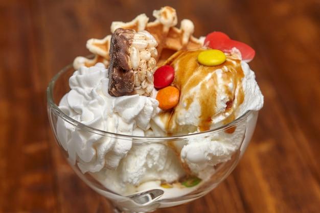 Cocktail di gelato in una ciotola con sciroppo e altre prelibatezze