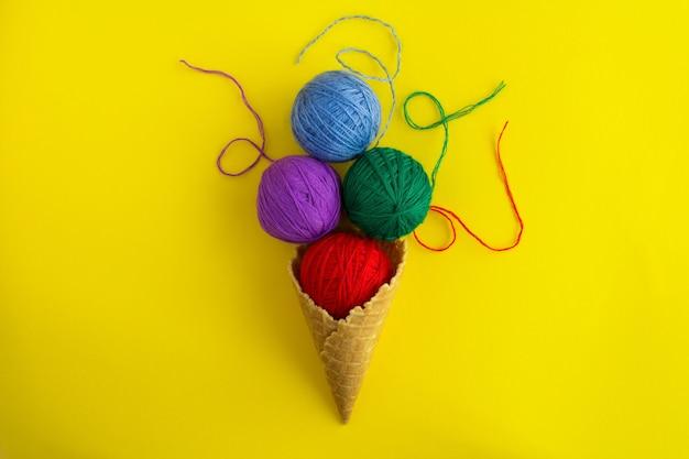 Cono gelato con fili colorati per lavorare a maglia al centro del tavolo giallo. vista dall'alto. copia spazio.