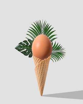 Cono gelato con uova e foglie di palma su bianco.