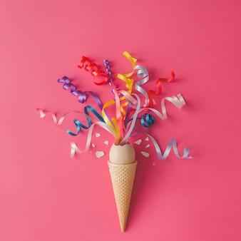 Cono gelato con uova e stelle filanti di partito sulla superficie rosa