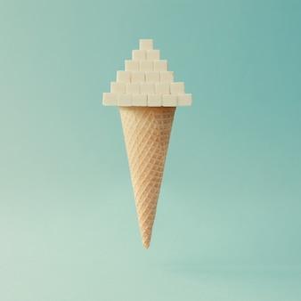 Cono gelato con cubetti di zucchero sulla superficie blu brillante