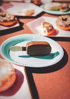 Gelato e ciambelle su piatti colorati su fondo marrone