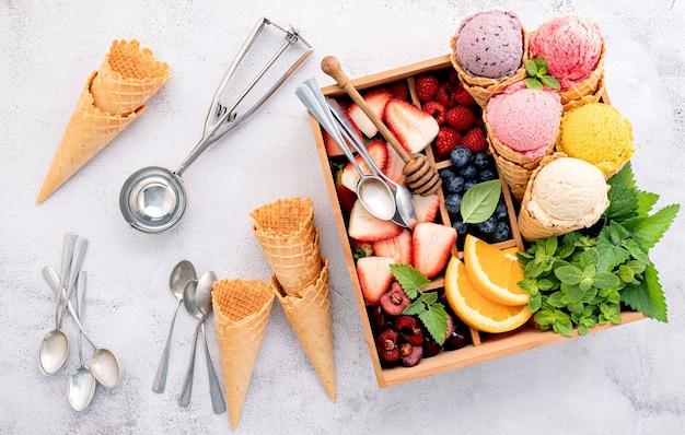 Sapore di gelato in coni con frutti di bosco in configurazione scatola di legno su sfondo concreto
