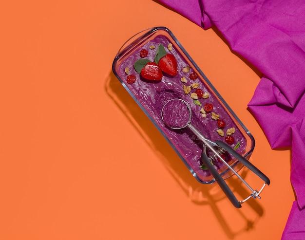 Sorbetto gelato ai frutti di bosco con cucchiaio su spazio arancione. copia spazio