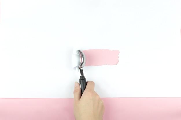Il cucchiaio di gelato in mano strappa un pezzo di carta bianca su uno sfondo rosa. concetto minimo. lay piatto, vista dall'alto, copia spazio.