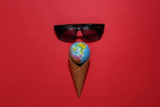 Cono di cialda gelato con globo, occhiali da sole su sfondo rosso brillante.