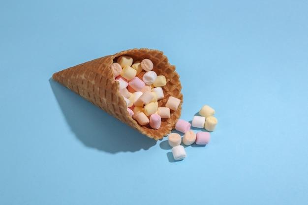 Cono di cialda gelato con marshmallow su sfondo blu pastello luminoso con ombra profonda