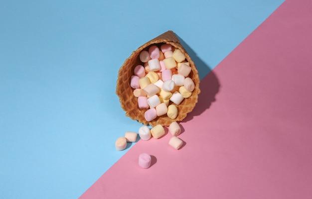 Cono di cialda gelato con marshmallow su sfondo pastello luminoso rosa e blu con ombra profonda