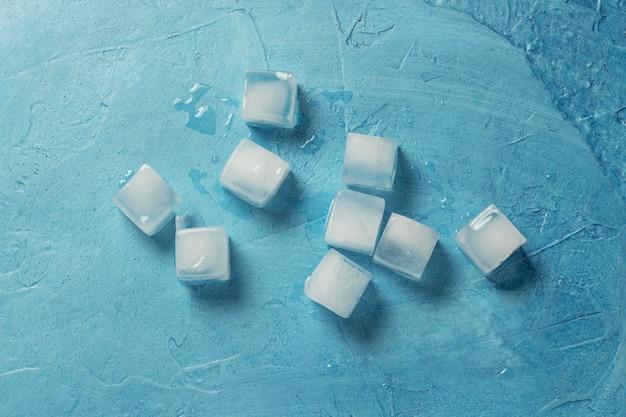 Cubetti di ghiaccio su uno sfondo di pietra blu. forma del quadrato concetto di produzione di ghiaccio. vista piana, vista dall'alto
