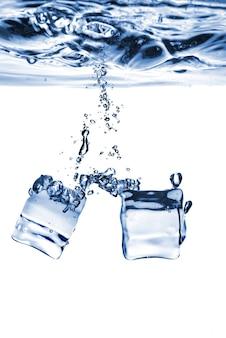 I cubetti di ghiaccio sono caduti in acqua con bolle isolate su bianco
