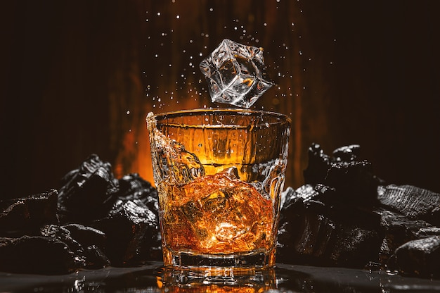 I cubetti di ghiaccio cadono in un bicchiere con una bevanda alcolica marrone