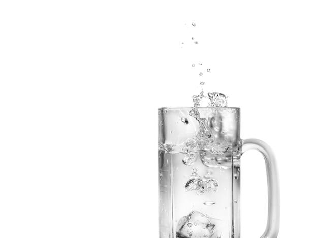 Cubetti di ghiaccio che cadono in un bicchiere con spruzzi d'acqua