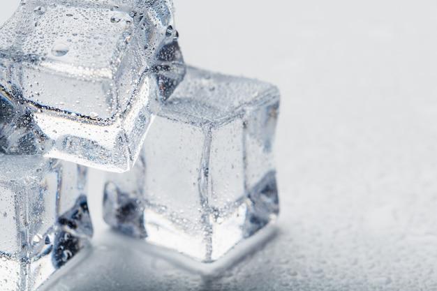 I cubetti di ghiaccio sotto forma di piramide con le gocce di acqua si chiudono - su nella macro su un fondo bianco.