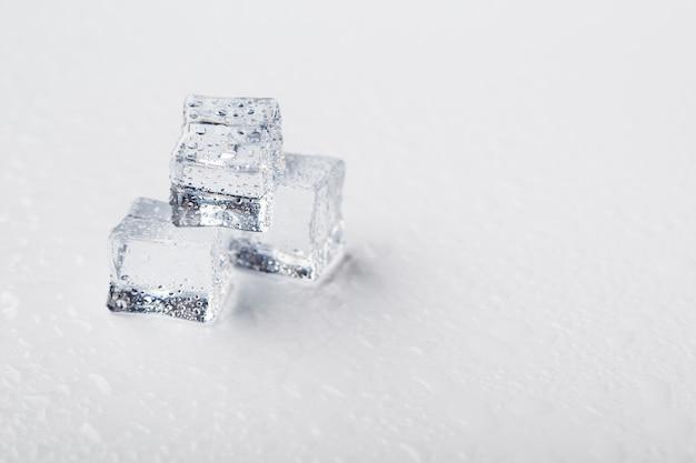 I cubetti di ghiaccio sotto forma di piramide con le gocce di acqua si chiudono - su nella macro