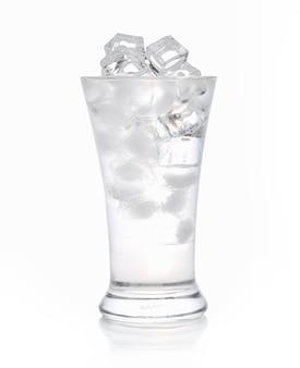 Cubetti di ghiaccio in un bicchiere d'acqua su bianco