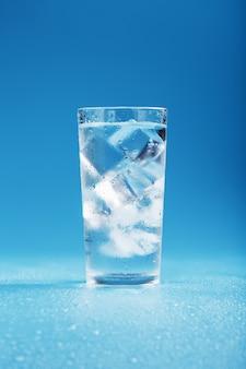 Cubetti di ghiaccio in un bicchiere con acqua cristallina su una superficie blu