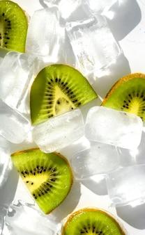 Cubetti di ghiaccio e fette di kiwi su uno sfondo bianco. la luce solare viene rifratta attraverso il ghiaccio.