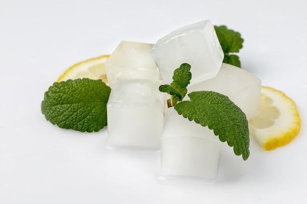 Cubetti di ghiaccio, fette di limone e foglie di menta, isolati su bianco