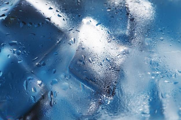 Cubetti di ghiaccio in un bicchiere appannato con gocce di macro close-up di acqua ghiacciata.