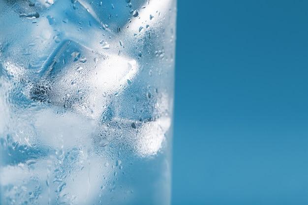 Cubetti di ghiaccio in un bicchiere appannato con gocce di macro close-up di acqua ghiacciata