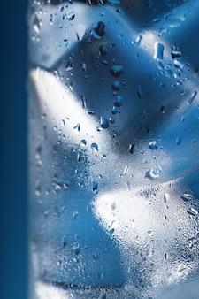 Cubetti di ghiaccio in un bicchiere appannato con gocce di acqua ghiacciata macro del primo piano