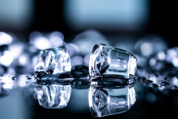 Riflessione di cubetti di ghiaccio su sfondo nero Foto Premium