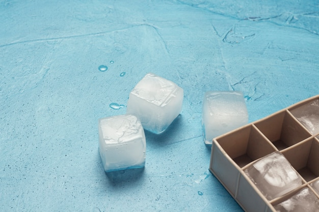 Cubetti di ghiaccio e stampo in silicone su uno sfondo di pietra blu. concetto di produzione di ghiaccio. vista piana, vista dall'alto