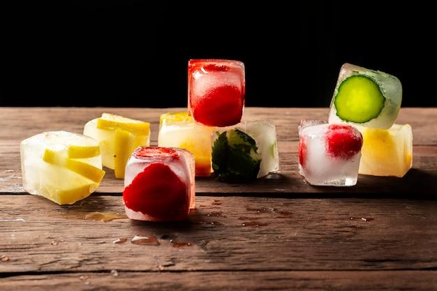 Cubetti di ghiaccio con frutta sulla tavola di legno. concetto di estate calda, dessert