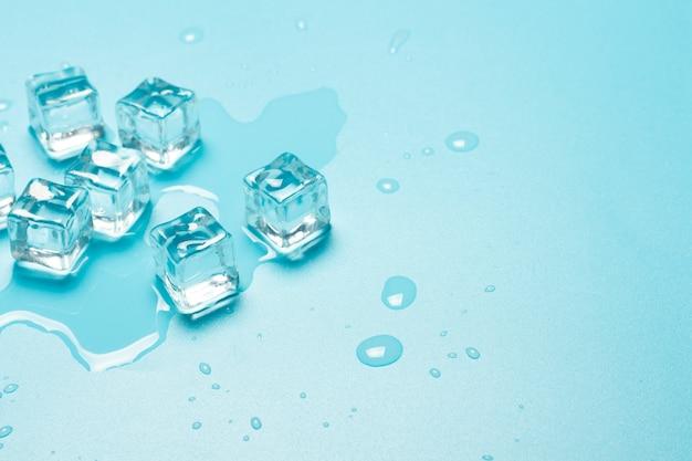 Cubetti di ghiaccio con acqua su uno sfondo blu. concetto di ghiaccio per bevande.