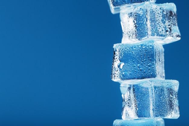 Cubetti di ghiaccio con gocce d'acqua torre di fila su uno sfondo blu.